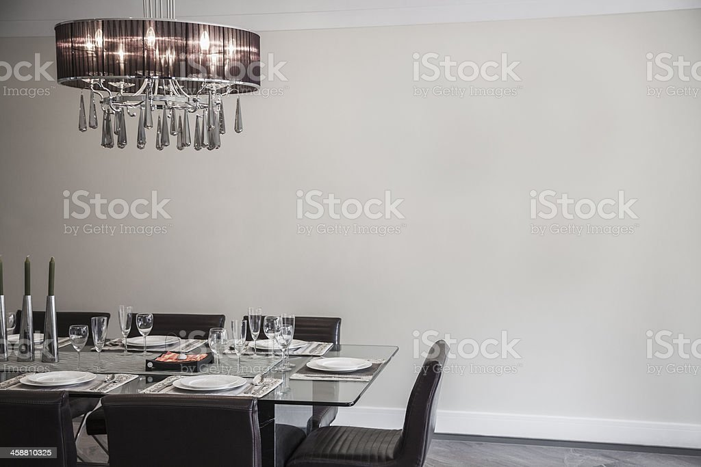 Modern dining room with a chandelier and table settings royalty-free stock photo