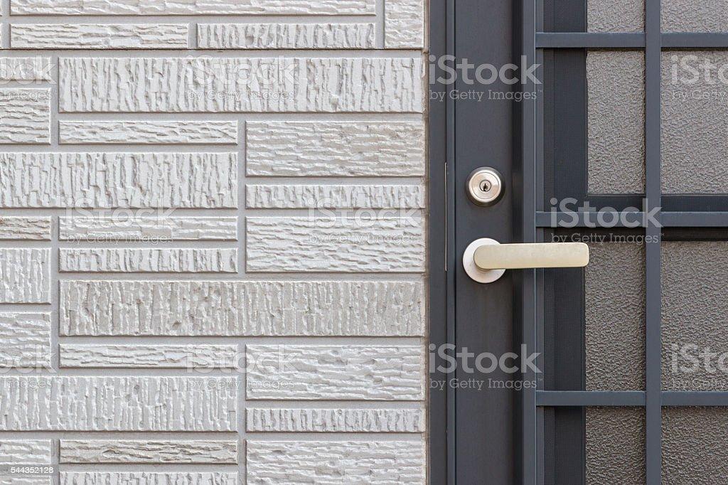 Modern door handle with key lock on black door stock photo