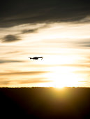 Modern drone silhouetted against sunset