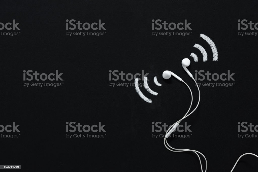 modern earphones with sound sign drawn on black chalkboard stock photo