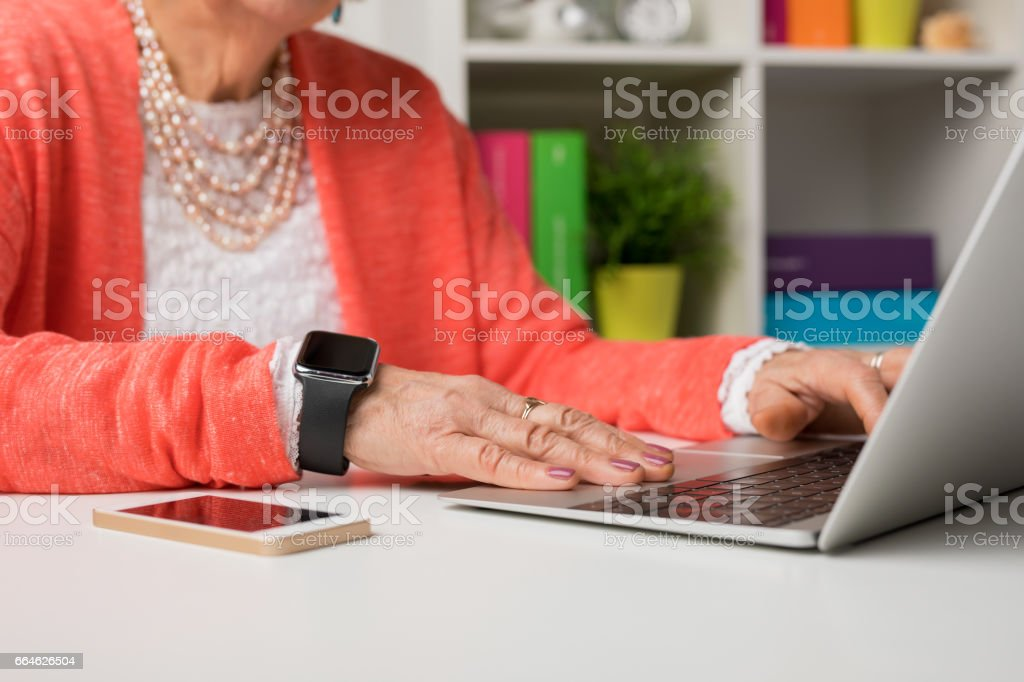 Modern elderly woman working at the office with laptop computer stock photo