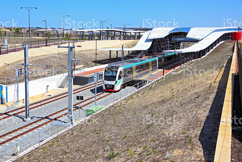 Modern electric commuter train departing new station stock photo