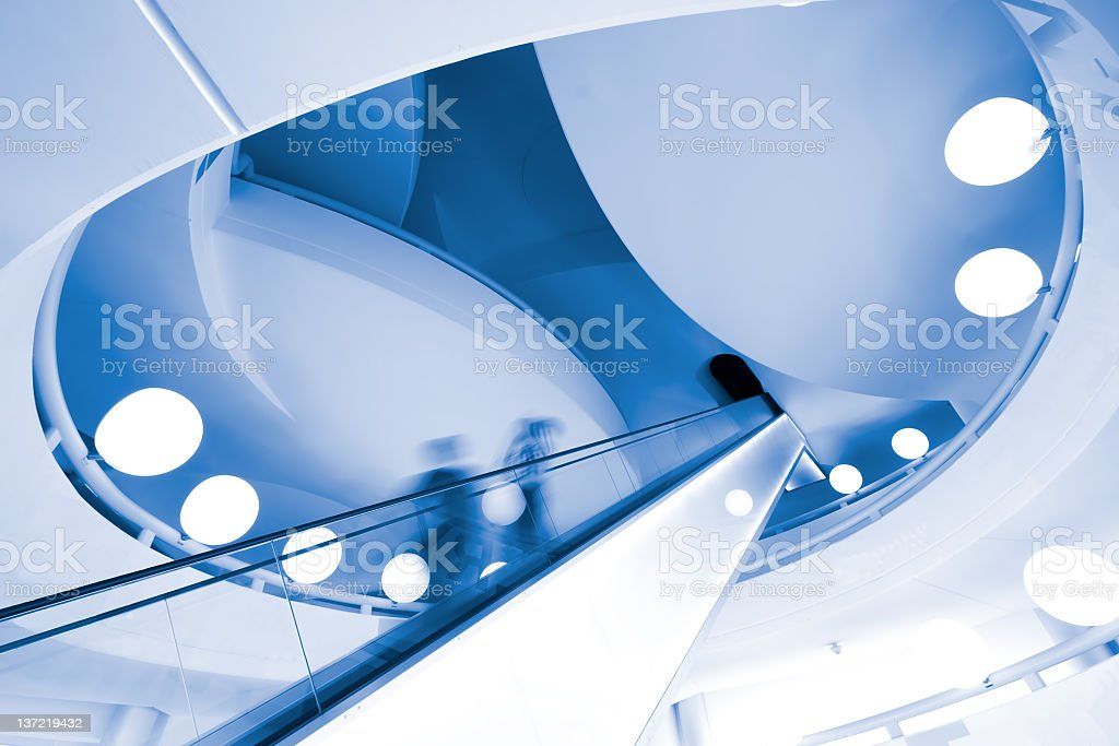 A modern escalator with blurry people going up royalty-free stock photo