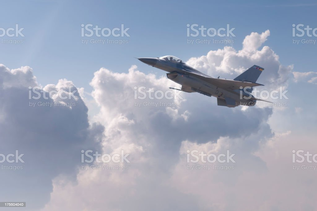 Modern F-16 fighter plane flying above the clouds stock photo