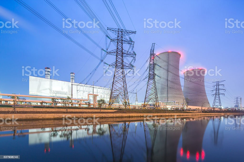 modern factory near river in blue sky at dawn stock photo
