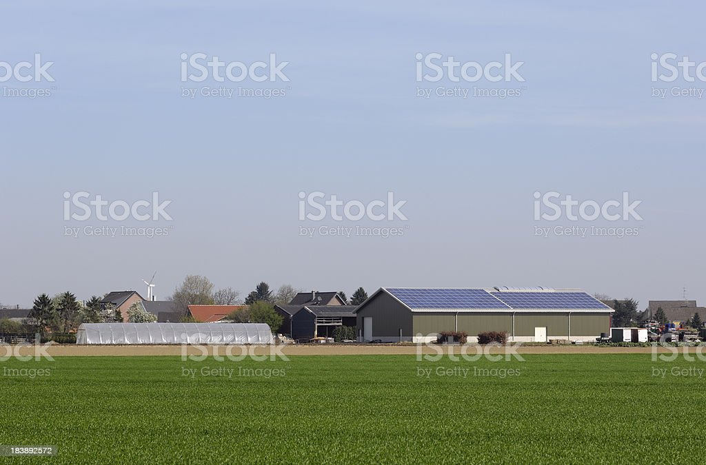 Modern farm with solar panels and a vernal field royalty-free stock photo