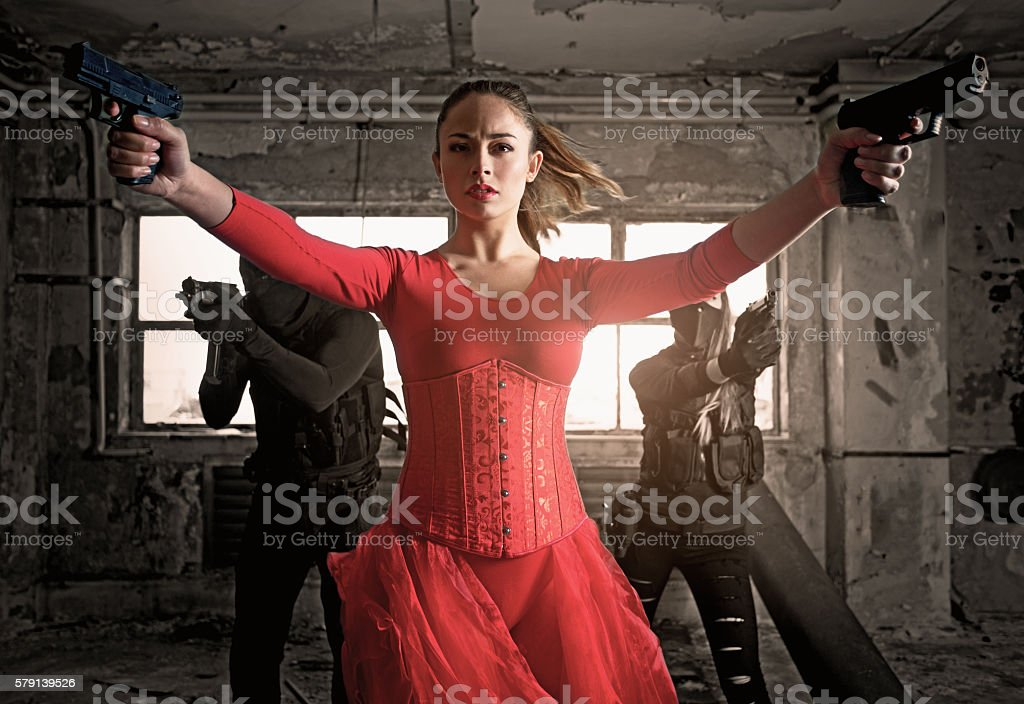 Modern female warrior wearing elegant red dress in urban setting stock photo