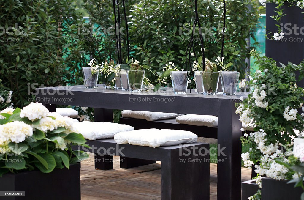 Modern furniture on outside deck with white flowers stock photo