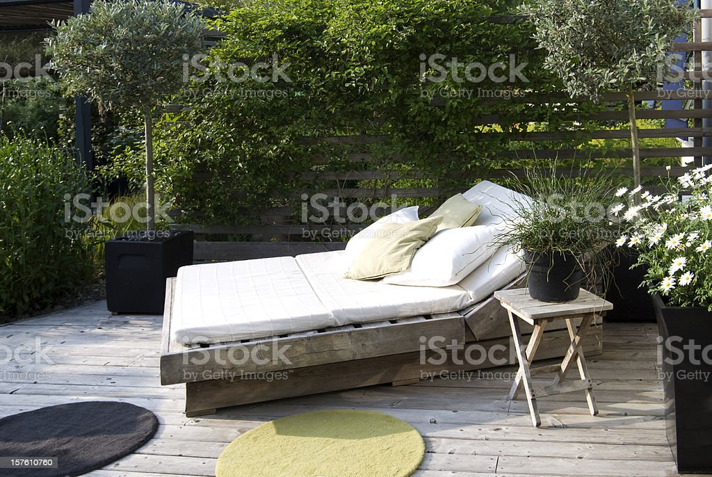 Modern garden with an outdoor bed in the afternoon sun royalty-free stock photo