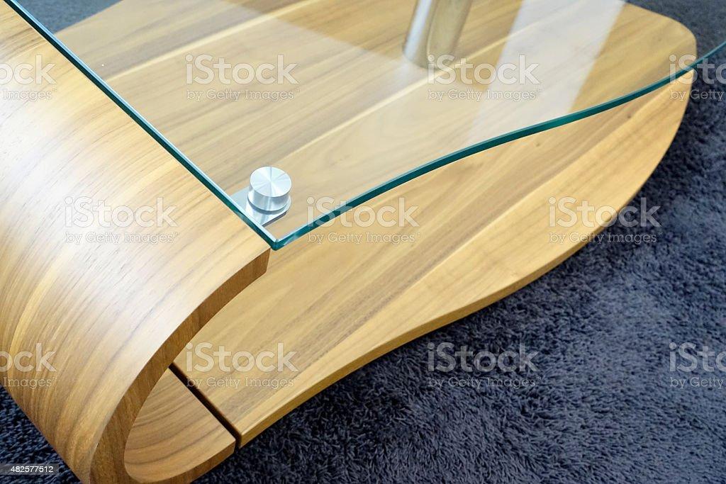 Modern glass wood table, standing on dark blue carpet stock photo