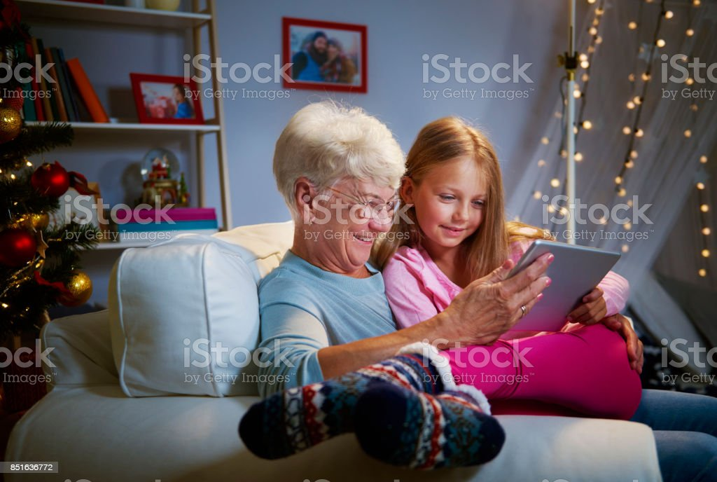 Modern grandmother and grandaughter  using a tablet stock photo