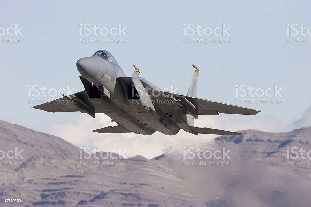 Modern Gray Jet Fighter with Mountains in the Background stock photo