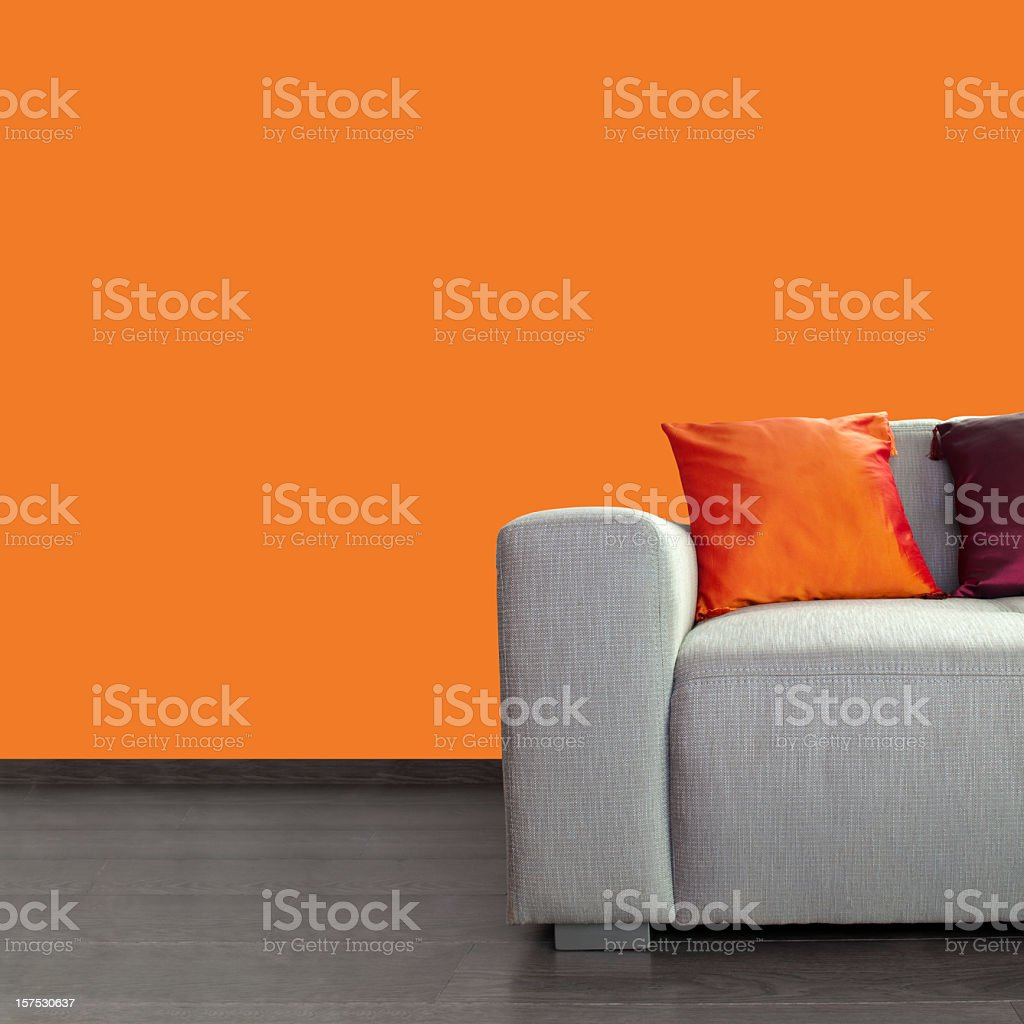 Modern gray sofa and colorful pillows against orange wall stock photo
