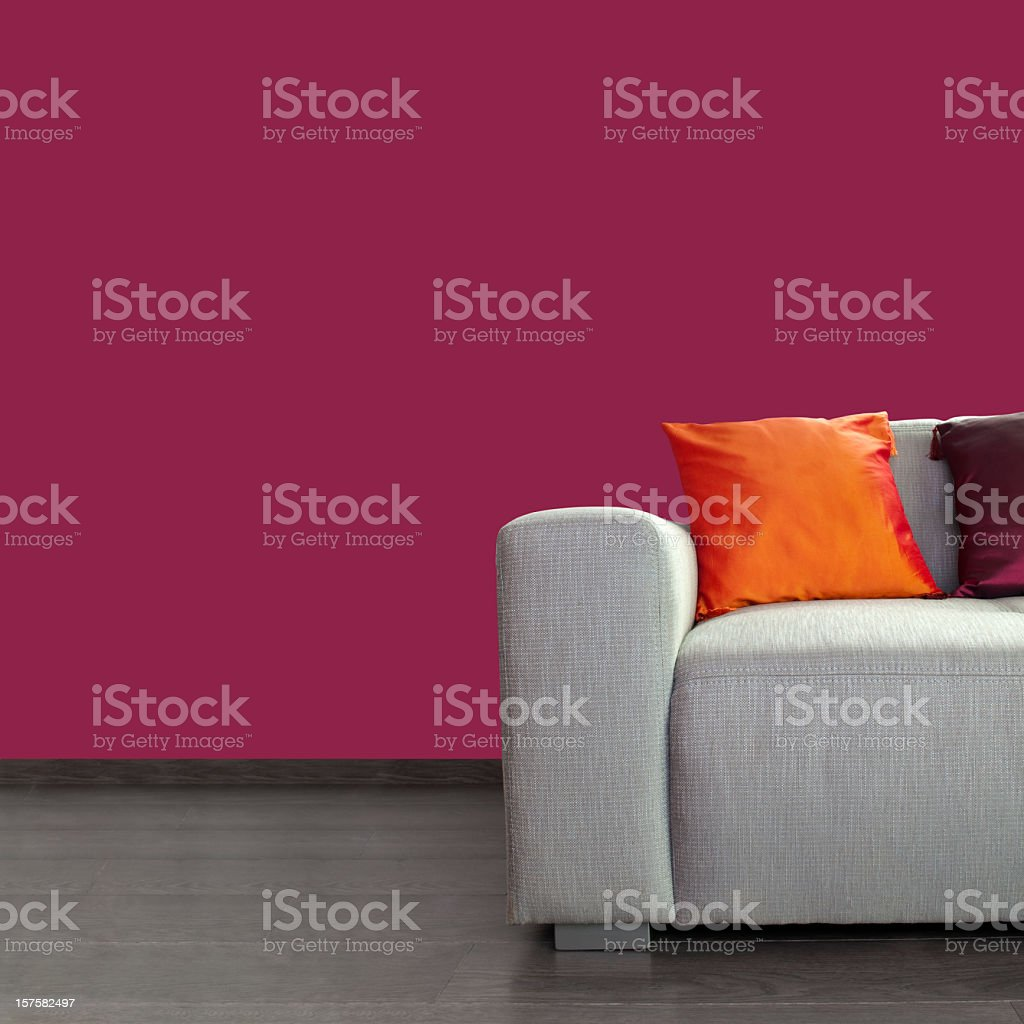 Modern gray sofa and colorful pillows against purple wall stock photo