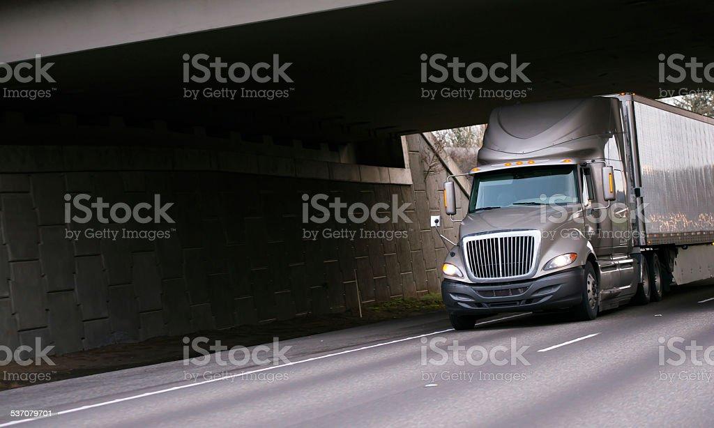 Modern grey semi truck under bridge on interstate highway stock photo
