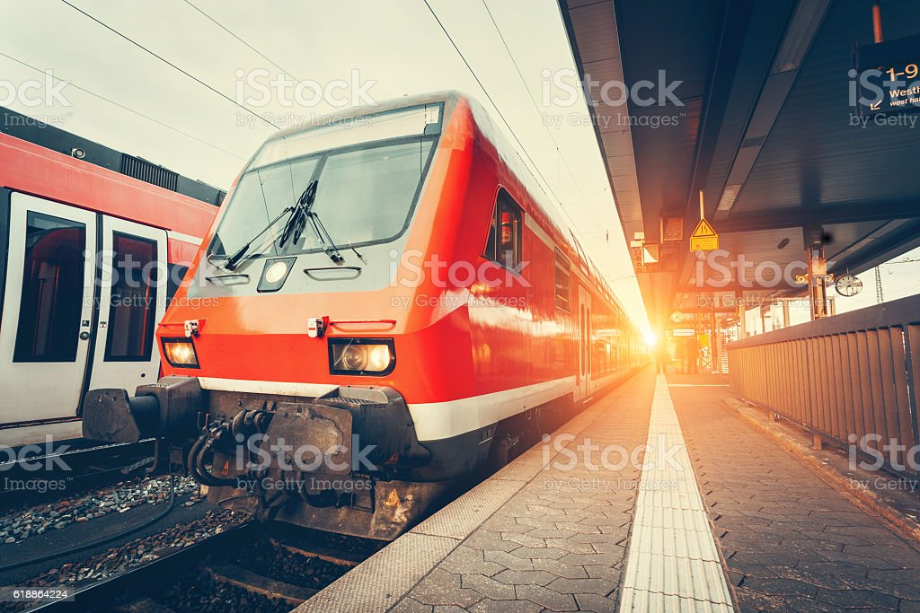 Modern high speed red commuter train at colorful sunset stock photo