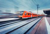 Modern high speed red passenger commuter train. Railway station