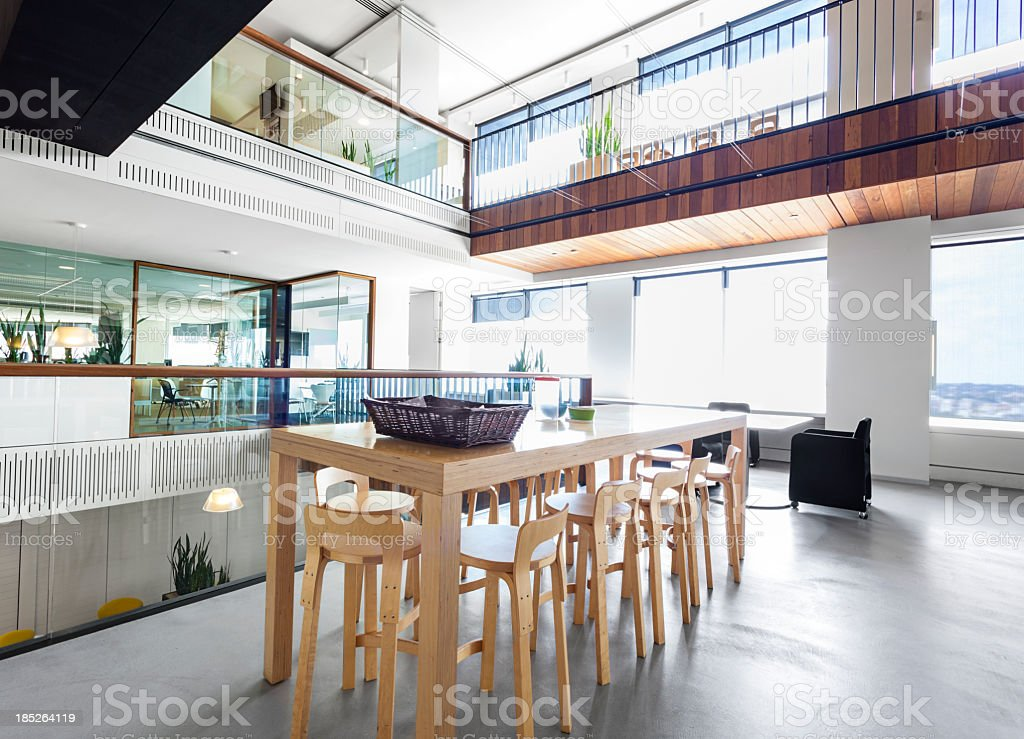 Modern, high wooden table in a large office space stock photo
