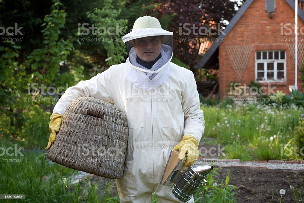 modern hobby for gardeners: beekeeper with beehive royalty-free stock photo