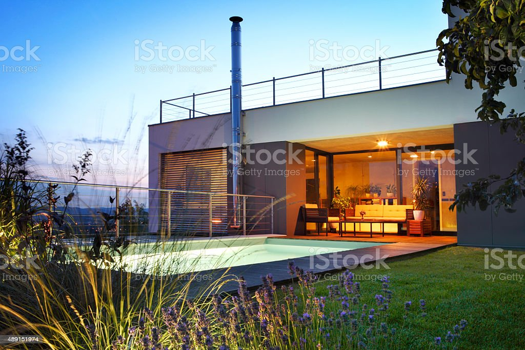 Modern house with swimming pool by twilight stock photo