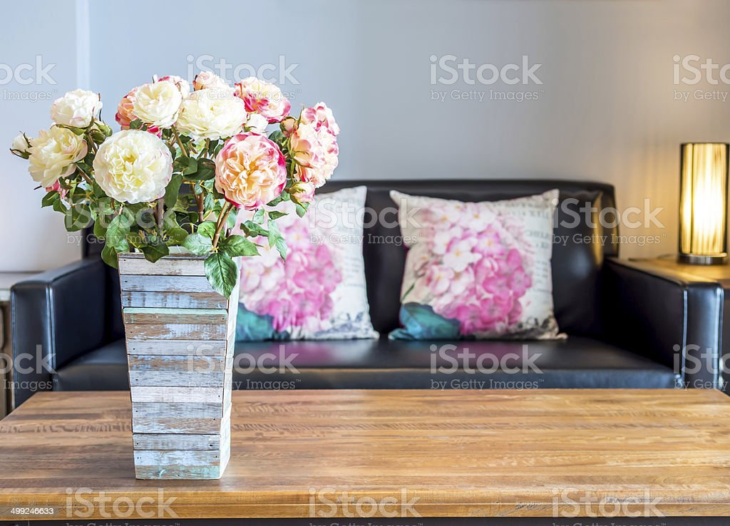 Modern interior room with artificial flowers in rustic wooden vase stock photo