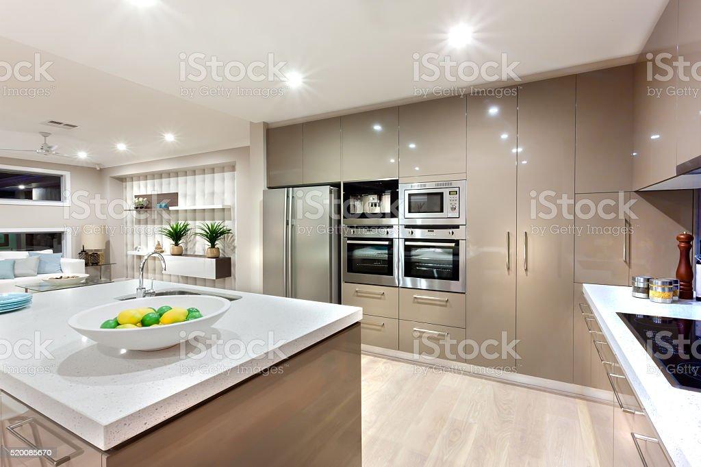 Modern kitchen area illuminated with lights at night stock photo