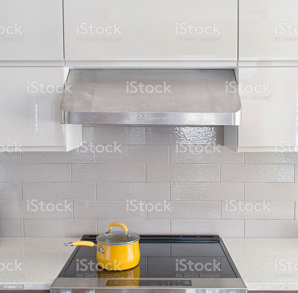 Modern kitchen range with yellow cooking pot stock photo