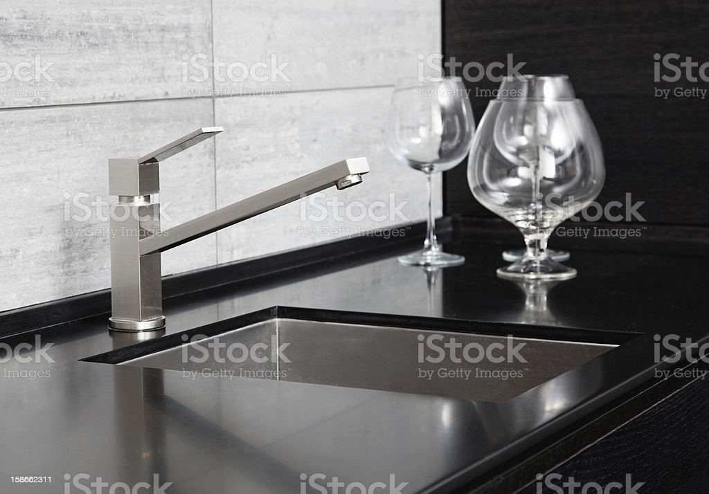 Modern kitchen sink with metal tap and black marble royalty-free stock photo