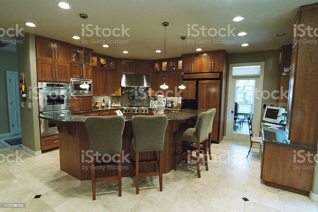 Modern kitchen with island style counters and wood cupboards stock photo