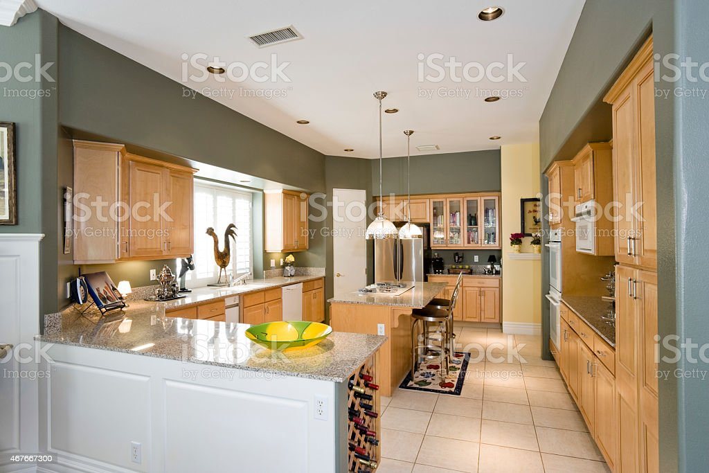 Modern Kitchen With Stools At Island In House stock photo