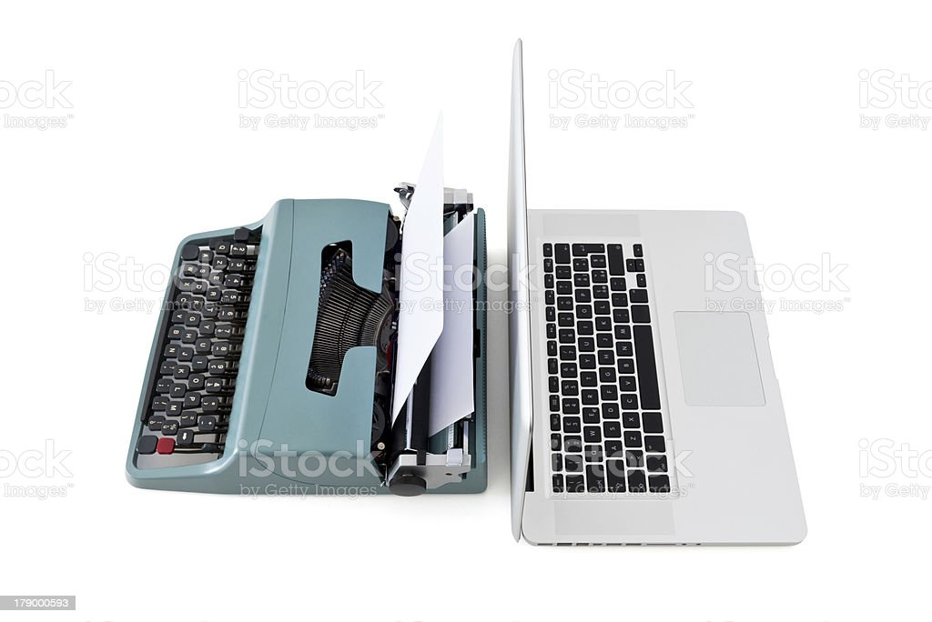 A modern laptop against a vintage typewriter stock photo