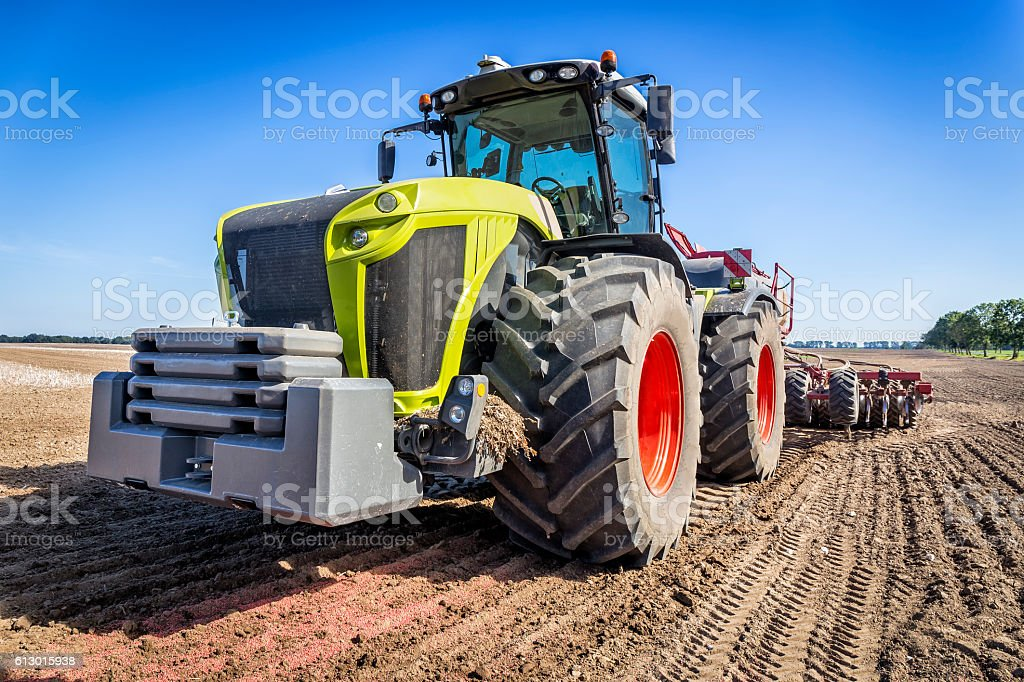 Modern large tractor plowing field stock photo