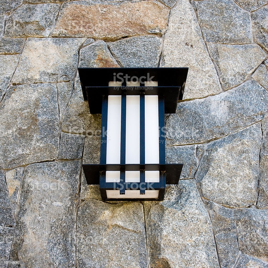 Modern Light Fixture Against Stone Wall royalty-free stock photo