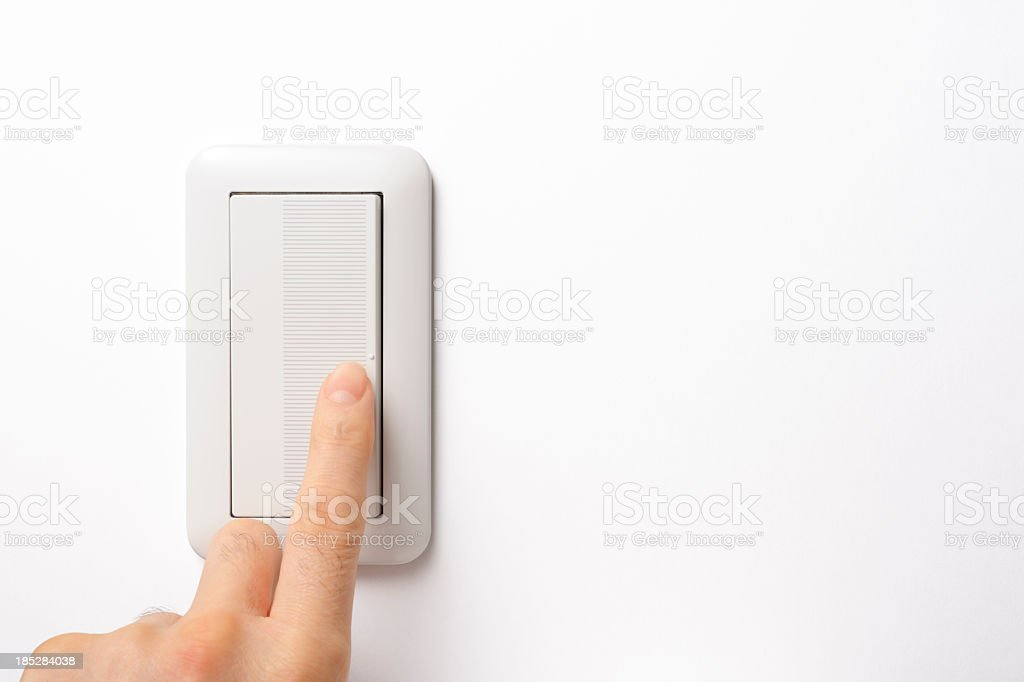 Modern light switch with finger on white background stock photo