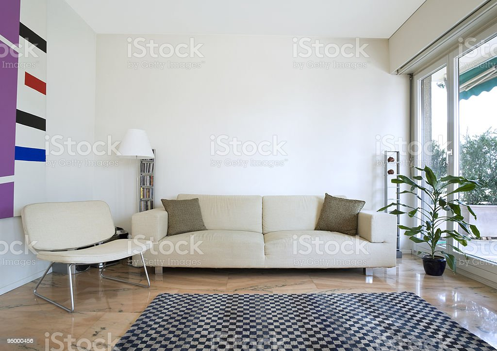 Modern living room with a couch, chair and plant royalty-free stock photo