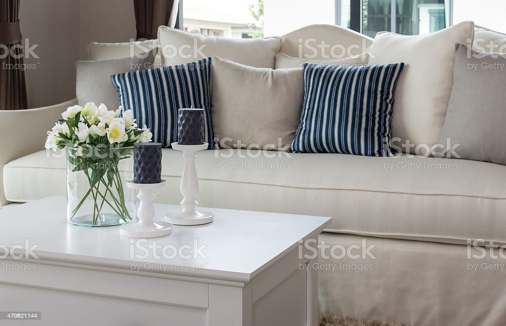modern living room with glass vase and row of pillows stock photo
