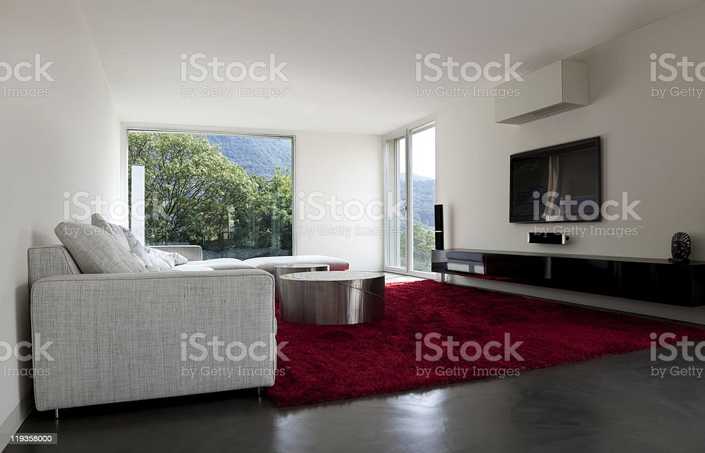 Modern living room with red carpet and green mountain view royalty-free stock photo