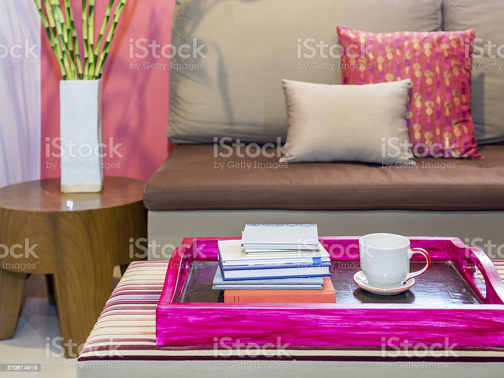 Modern living room with sofa, coffee cup in colorful tray stock photo