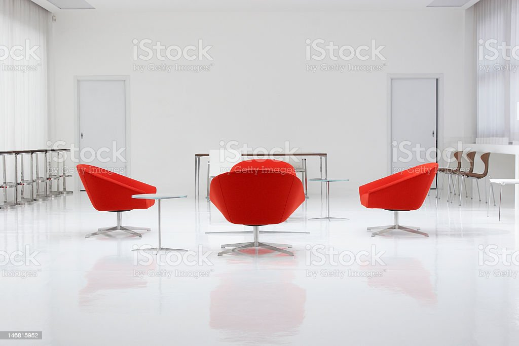 A modern loft with red chairs and white walls royalty-free stock photo