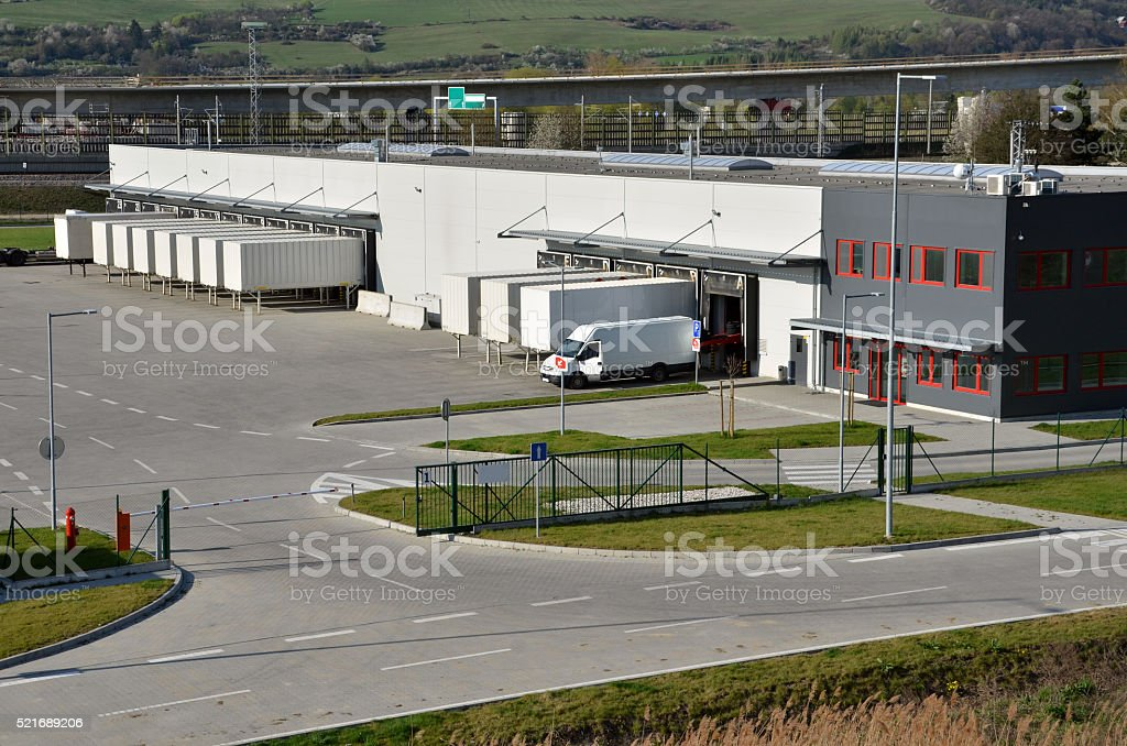 Modern logistics center, white van and trailers standingon ramp stock photo