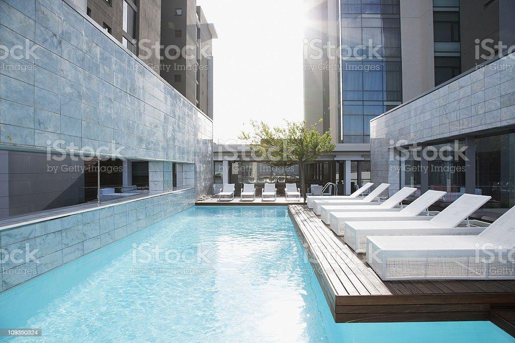 Modern lounge chairs next to swimming pool stock photo