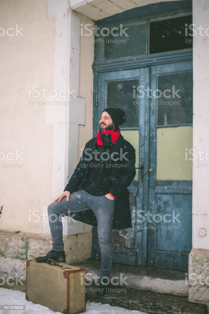 Modern man standing in the station with an old suitcase stock photo