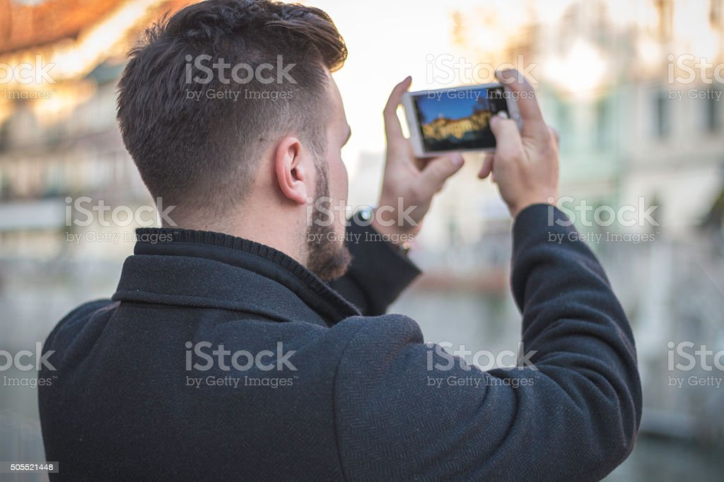 Modern man taking picture of the city stock photo