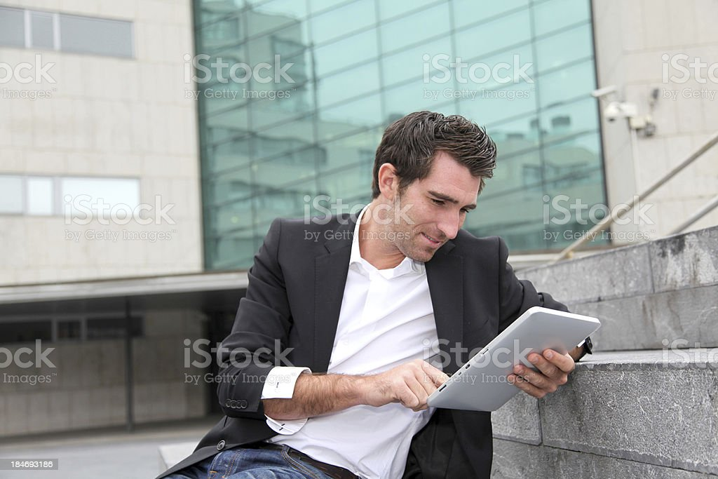 Modern man with tablet in hand sitting on stairs royalty-free stock photo