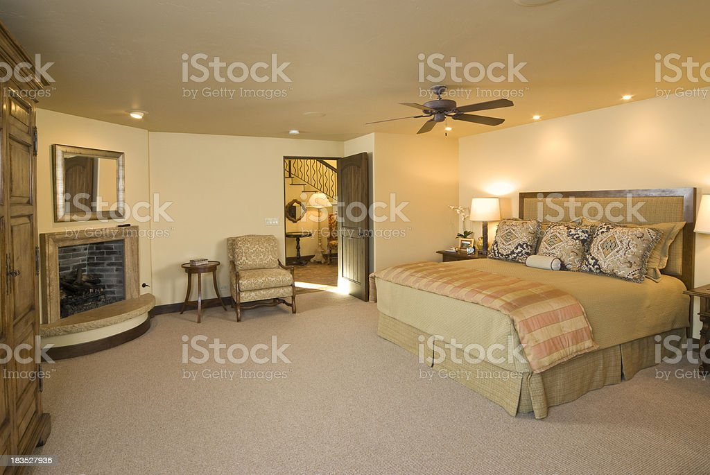 Modern master bedroom with stone fireplace royalty-free stock photo