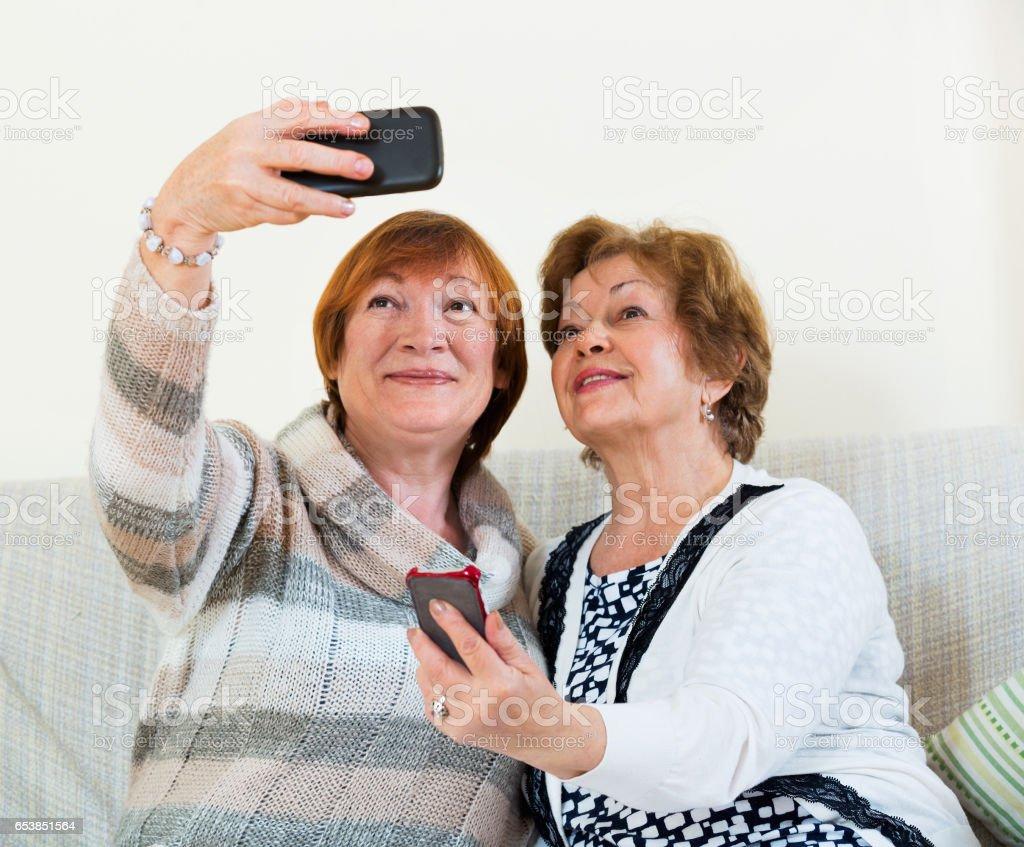 Modern mature women using mobile phone stock photo