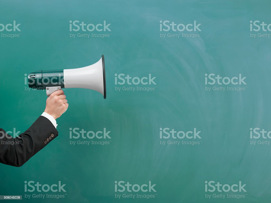 Modern Megaphone In Human Hand On Green Blank Blackboard stock photo