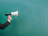Modern Megaphone In Human Hand On Green Blank Blackboard