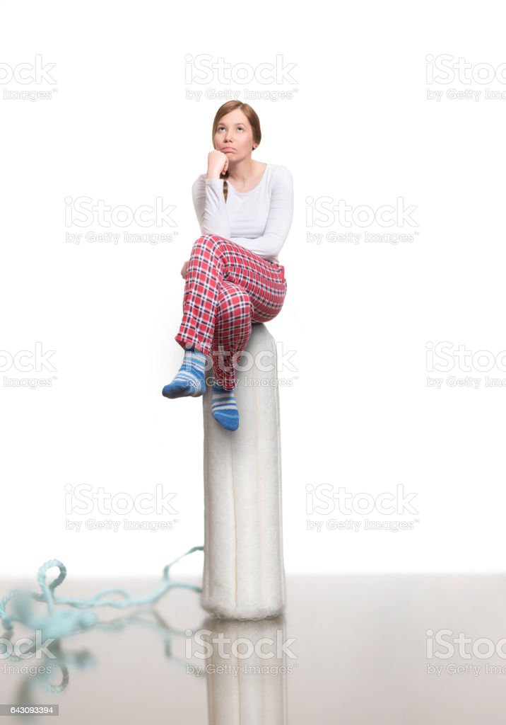 Modern Menstruation- Young woman sitting on top of tampon stock photo