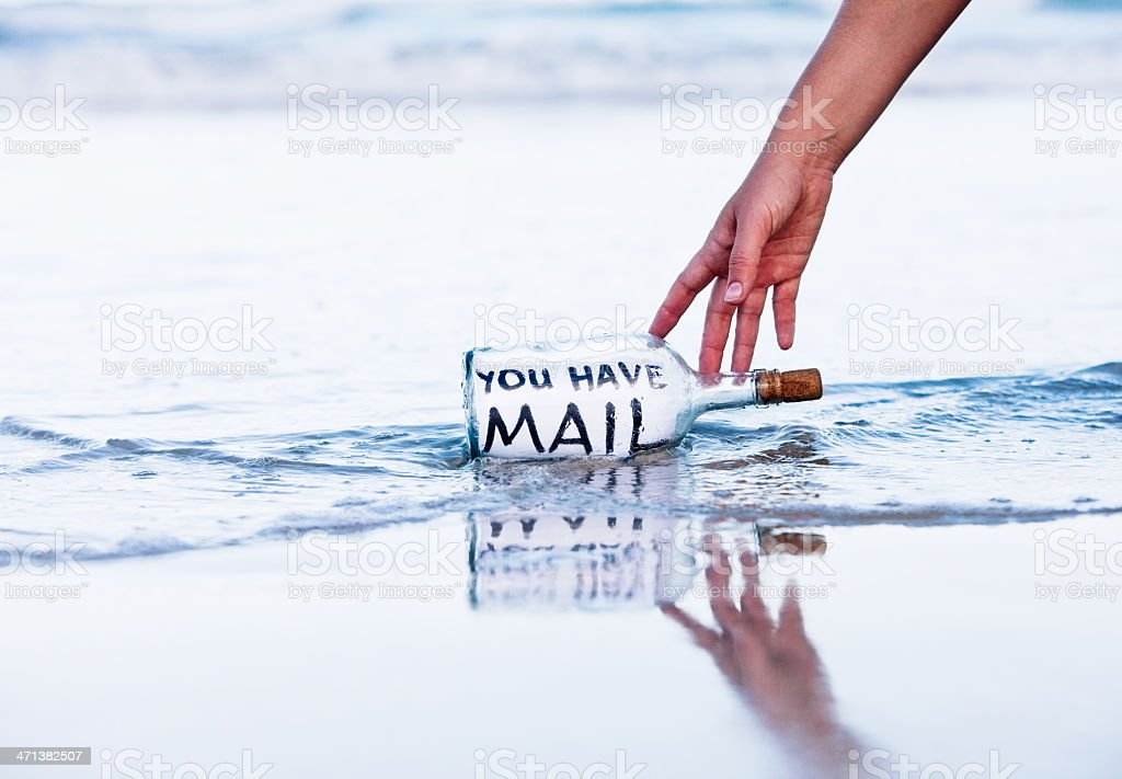 Modern message in bottle on beach says You have mail stock photo